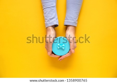 Female hands with gift box on color background #1358900765