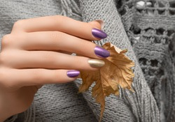 Female hands with gold nail design. Red nail polish manicured hands. Woman hands hold yellow autumn leaf