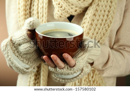 Female hands with hit drink, on color background