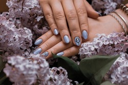 Female hands with lilac, artistic manicure lie on the flowers of lilac