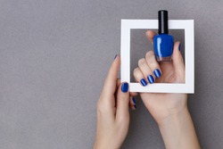 Female hands with manicure in trendy classic blue color holding white frame and a bottle of nail polish on the grey background