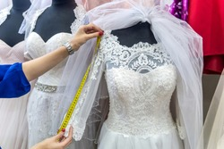 Female hands with measuring tape and wedding dress