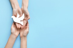 Female hands with paper dove on color background. International Day of Peace