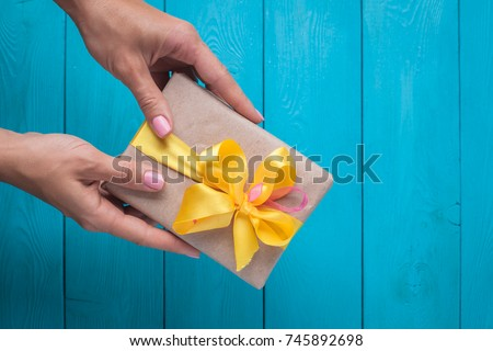 Female hands with pink manicure holding a beautifully wrapped gift with a yellow bow on the blue background.