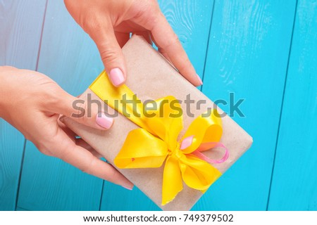 Female hands with pink manicure holding a beautifully wrapped gift with a yellow bow on the blue background. Lighting a bright flash.