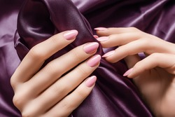 Female hands with pink nail design. Pink nail polish manicured hands. Woman hands hold purple fabric