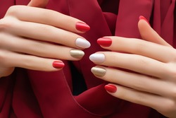 Female hands with red nail design. Gold and white nail polish manicure. Woman hands on red fabric background
