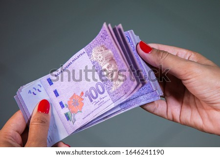 Female Hands with red nails counting 100 Ringgit banknotes. Ringgit the currency of Malaysia. Woman hands showing RM100 notes. Close up to the Malaysian money with colorful fingernails
