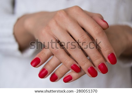 Female hands with red nails on a white background. On her nails red manicure.