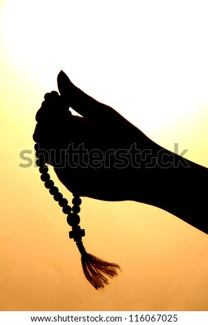 female hands with rosary, on beige background