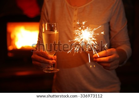 Female hands with sparkler and glass of sparkle wine on fireplace background #336973112