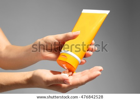 Female hands with sun protection lotion on grey background #476842528