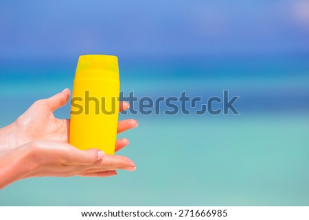 Female hands with suncream bottle background blue sea #271666985
