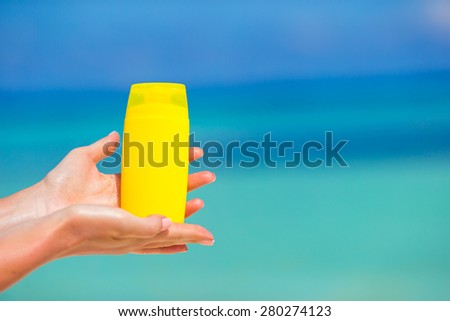 Female hands with suncream bottle background blue sea #280274123
