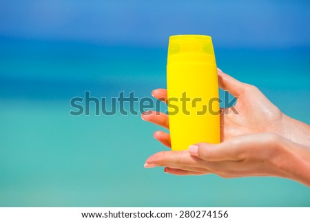 Female hands with suncream bottle background blue sea #280274156