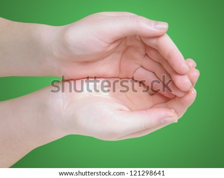 female hands with water over green