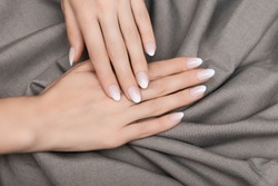 Female hands with white nail design. White glitter nail polish manicure. Woman hands on grey fabric background.