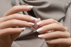 Female hands with white nail design. White glitter nail polish manicure. Woman hands on grey fabric background