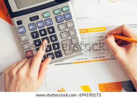 Female hands working with documents and calculator - Shutterstock ID 694190173