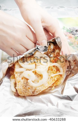 Female hands wrapping raw chicken meat marinated with pieces of fresh onion on aluminum food foil, selective focus - stock photo