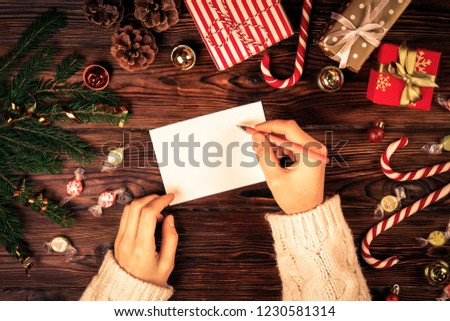 Female hands writing letter to Santa Claus on wooden background with christmas gifts and decoration top view. Vintage toned image with woman, wish list for christmas, flat lay, copy space, background. #1230581314