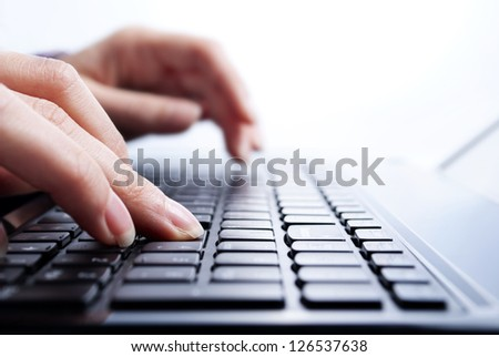 female hands writing on laptop, close-up shot