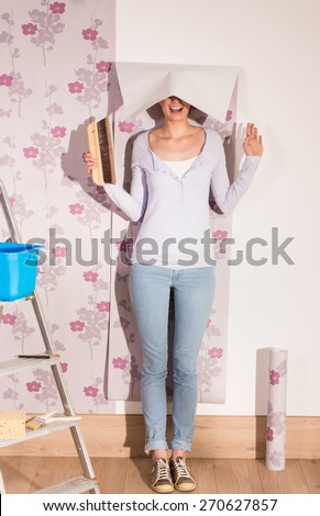 female handyman enjoys to take a funny pose with her tools and a piece of wallpaper falling on her head #270627857