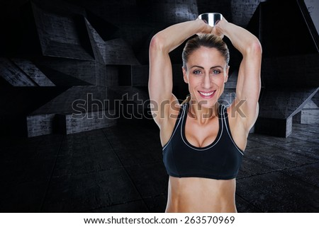 Female happy bodybuilder working out with large dumbbell behind head against dark room