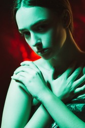 Female harassment. Domestic violence. Humiliation misery. Art portrait of ashamed woman covering bare shoulders with hands in blue neon light on dark red glowing background.