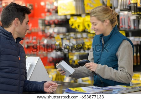 female hardware store seller scanning clients item