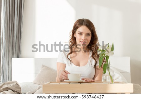 Female having breakfast sitting in bed