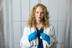 Female Health care worker in a lab coat and scrubs standing with a stethoscope