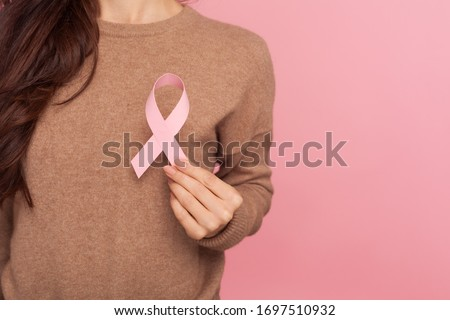 Female health check awareness. Closeup of young woman in pullover holding pink ribbon, symbol of breast cancer, timely diagnosis, support of oncology patients. studio shot isolated on pink background