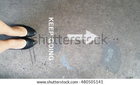 Female high heels on the cement road with a drawing direction arrow with the word keep going Foto d'archivio ©