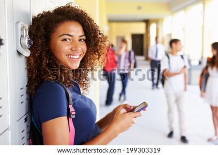 Female High School Student By Lockers Using Mobile Phone