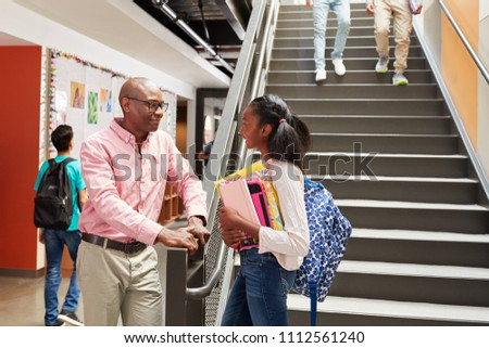 Female High School Student Talking With Teacher In Busy Corridor