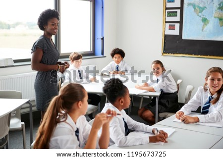 Female High School Tutor Helping Students Wearing Uniform Seated Around Tables In Lesson