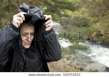 female hiker cold and wet near river using her hood to shelter from the rain