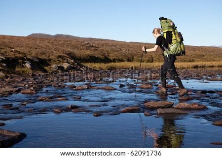 female hiker cross the river