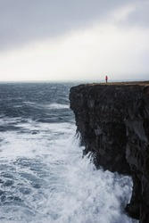 Female hiker girl woman in pink red jacket standing on top of Hafnaberg lava sea cliff in Hafnir Reykjanes Southern Peninsula Reykjanesskagi Iceland Europe