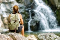 Female hiker looking at waterfall.