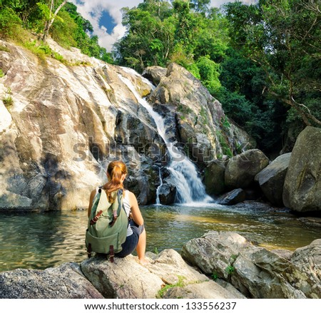 Female hiker looking at waterfall. stock photo