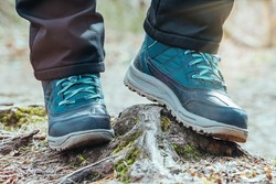 Female hiker on a hiking trail in forest, view from the ground of legs and boots walking.