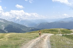Female hiker on a trail in Svaneti region, Georgia, Asia. Summer mountain landscape with snowcapped mountains in the background. Blue sky with clouds above. Georgian tourist destination.