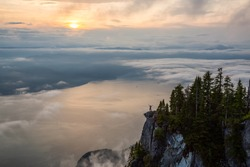 Female Hiker on top of a mountain covered in clouds during a vibrant summer sunset. Taken on top of St Mark's Summit, West Vancouver, British Columbia, Canada.