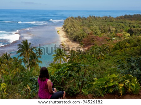 Female hiker overlooking Kee beach from Kalalau trail on Na Pali coast of Kauai