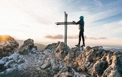 Female hiker reaching her goal at the mountain top and near the summit cross. Satisfy hiker enjoy view. Concept of freedom, journey, active lifestyle. Human and nature