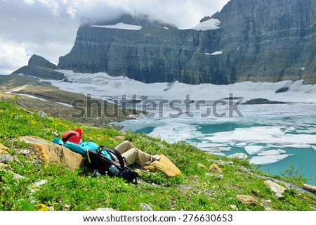 female hiker resting by the Grinnell glacier in Many Glaciers, Glacier National Park, Montana in summer