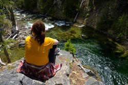 Female Hiker Sitting On Cliff Above Scenic River