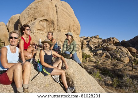 Female hiking team climbs to the summit of a challenging rock spire in Joshua Tree National Park.